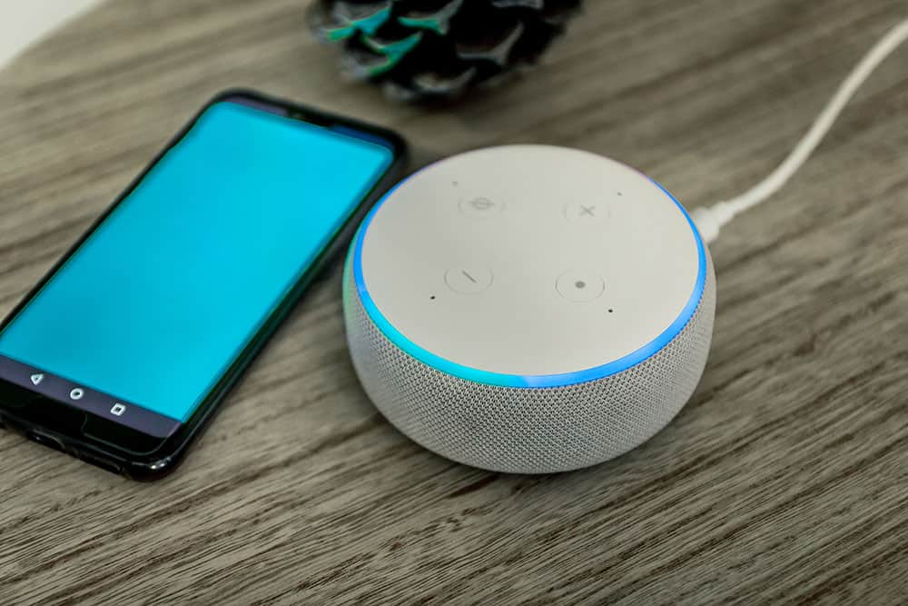 voice assistant speaker with cell phone on table