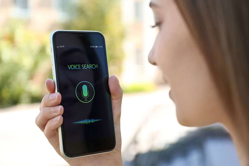 young woman performing a voice search on her cell phone
